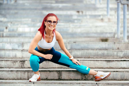 Attractive young active woman smiling and working out on stairs. Stretching and running training. Fitness concept