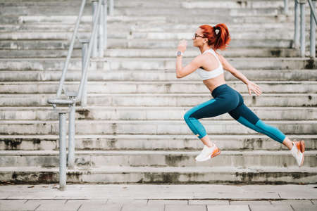 Portrait of sportswoman with fit body jumping and running on stairs background. Woman doing hardcore cardio training