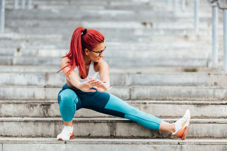 Attractive casual active woman smiling and working out on stairs. Stretching and running training. Fitness concept