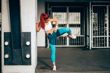 woman in sports clothing listening to music on smartphone., doing workout exercises and stretching