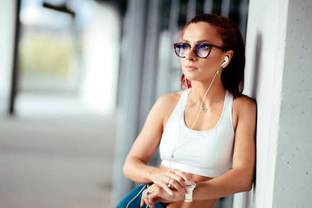 Portrait of smiling woman listening to music and training with smartwatch