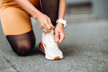 Close-up of active jogging female runner, preparing shoes for training and working out at fitness workout Stock fotó