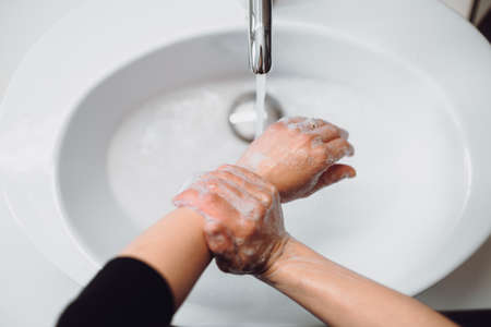 Close up details of woman scrubing and washing hands at home . Hygiene and body cleaning concept detail
