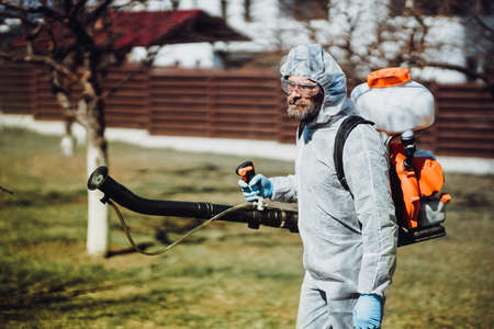Portrait of industrial worker wearing protective clothing and spraying pesticides, insecticides and other organic chemicals