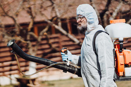 Portrait of industrial worker wearing protective clothing and spraying pesticides, insecticides