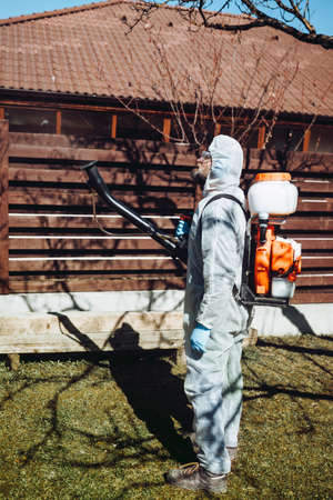 Agriculture farmer using machine, mistblower for pesticides and insecticide spraying  and wearing protective clothing