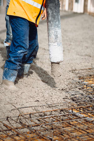 Details of construction site. worker pouring concrete with automatic pump