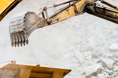 track type excavator industrial scoop loading dumper truck. engineer working with excavator at open mine ore