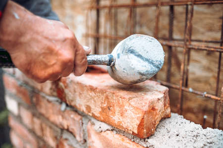 Industrial worker,  construction worker laying bricks and building walls on construction site. Detail of hand adjusting bricks with rubber hammer 版權商用圖片