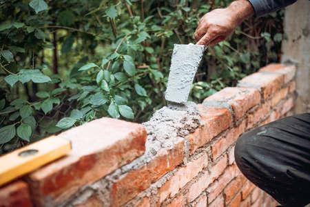 Construction bricklayer worker building with bricks, mortar, trowel. Industry details 版權商用圖片