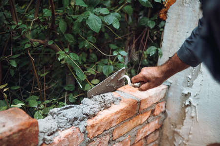 Bricklayer placing and adjusting bricks with mortar, putty knife and trowel. Professional construction worker building exterior walls