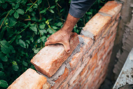 Close up of man, industrial bricklayer installing bricks on construction site