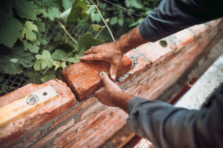 professional construction worker laying bricks and building walls in industrial constructiuon site. Detail of hand adjusting bricks 版權商用圖片