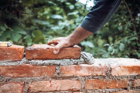 industry details - Construction bricklayer worker building walls with bricks, mortar and putty knife 版權商用圖片