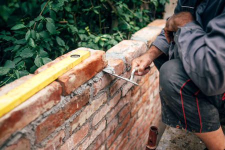 Construction site details - builder working with hands, level and trowel and building brick walls