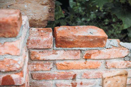 Details of exterior brick walls being build. Construction site with bricks and mortar 版權商用圖片