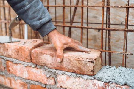 details of worker, bricklayer placing and adjusting bricks. Professional construction worker building exterior walls