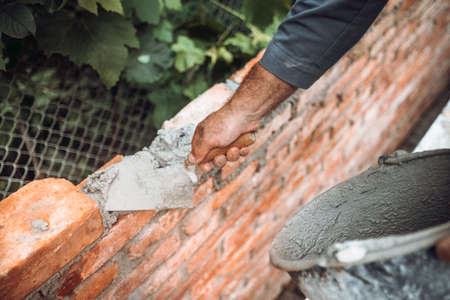 industrial Construction bricklayer worker building walls with bricks, mortar and trowel