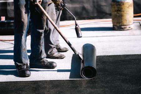 Construction workers, roofers installing rolls of bituminous waterproofing membrane for the waterproofing of new house. House waterproofing and insulation 版權商用圖片