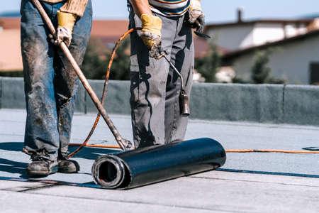 Rooftop waterproofing details. Workers installing bituminous membrane waterproof system insulation 版權商用圖片