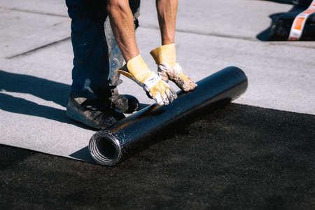 Professional workers waterproofing house construction site. Worker rolling membrane 版權商用圖片