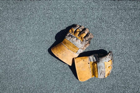 Details of waterproofing at house construction. Fire resistant gloves