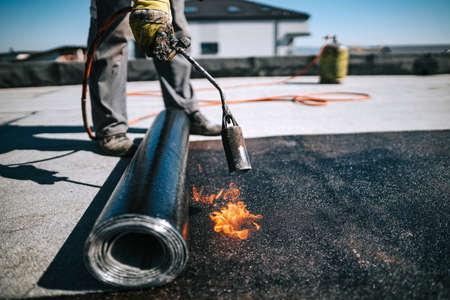 Professional workers insulating rooftop with bitumen membrane. Waterproofing details at construction site. Bituminous membrane waterproofing system details and installation on flat rooftop.