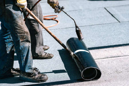 Construction workers, roofers installing rolls of bituminous waterproofing membrane for the waterproofing of new house. House waterproofing details with professional workers