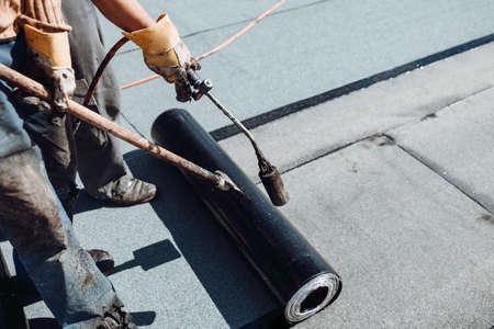 Workers waterproofing flat concrete roof using blowtorch and bituminous membrane rolls 版權商用圖片