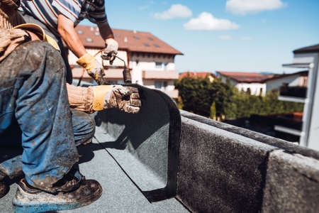 Professional construction worker  installing and waterproofing flat roof at house construction site. Bituminous membrane waterproofing  system installation 版權商用圖片