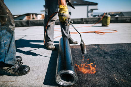 Bituminous membrane waterproofing system details and installation on rooftop. Professional construction worker installing and waterproofing house construction.