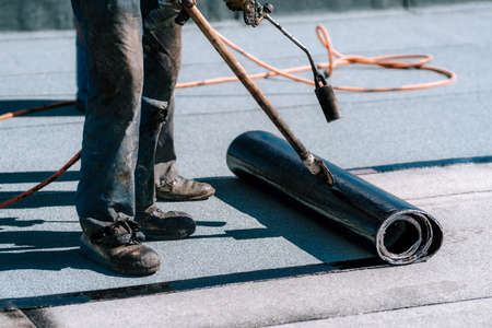 Workers insulating roof at house construction using bituminous membrane waterproofing system