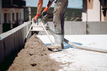 Screed details. Construction site details with workers, cement, mortar and sand 版權商用圖片