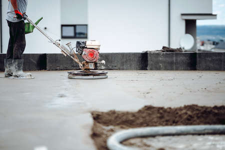 cement smoothing trowel machinery with worker. screed, flooring smoothing at  house construction site