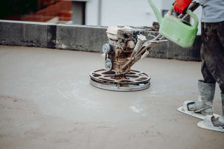 Helicopter concrete floor finishing on construction site. Construction worker finishing concrete screed with power trowel machine Stock Photo