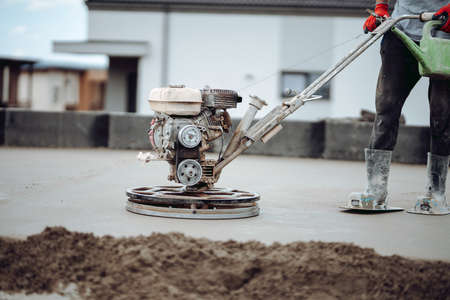 Helicopter concrete floor finishing on construction site. Construction worker finishing concrete screed with power trowel machine 版權商用圖片