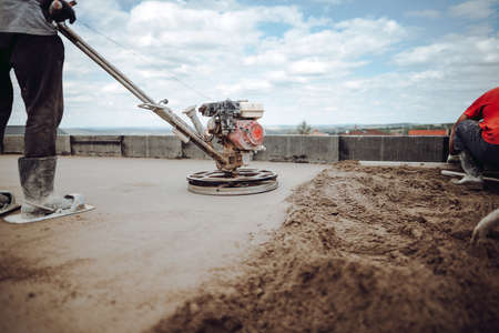 Laborer working on a floor screed on roof terrace
