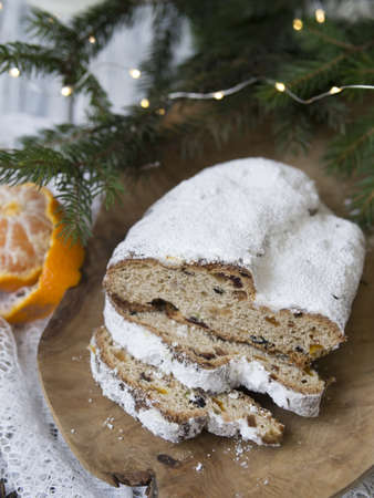 Traditional European Christmas pastry, fragrant home baked stollen, with spices and dried fruit. Sliced on wooden table with xmas tree branches and decorations, copy space, selective focus