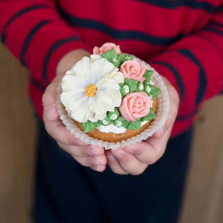 Homemade sponge cupcakes with flowers buttercream frosting. The boy is holding decorated cupcake. Sweet gift to mom,teacher or girlfriend for March 8, Valentines Day or Teachers Day.Selective focus