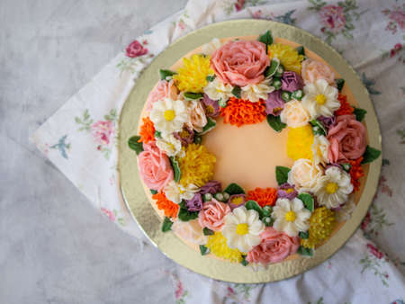 Yellow cream cake decorated with buttercream flowers - peonies, roses, chrysanthemums, carnations - on white wooden background. Card for March 8, Womens Day, Valentines Day. Copy space, top view