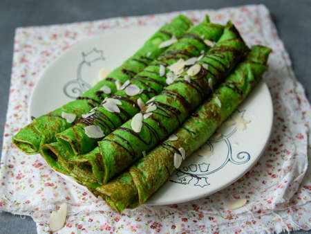 Mint thin crepes of green color, twisted into tubes, with chocolate sauce and almond petals on a white plate on gray background with floral fabric. Exquisite breakfast. Close up, selective focus.. Imagens