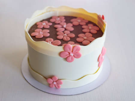 Cake with a chocolate decor - chocolate white boards and pink chocolate flowers. Cake for birthday, anniversary and any other holiday. White background, isolated. Selective focus, close up.
