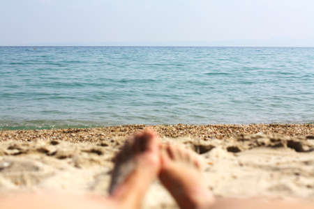 Female feet, sandy beach and sea in the background. Picture with soft focus and place for your text. summer concept. Enjoying the sea or ocean. Focus is on the sea. Vacation holidays. Copy space Stockfoto