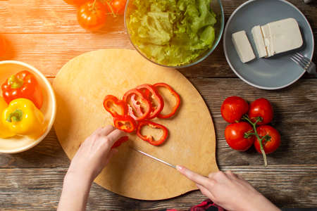 hands of a girl cut bell pepper on a wooden table, the process of making vegetarian salad, close-up cutting of vegetables and greens