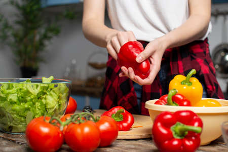 young girl prepares a vegetarian salad in the kitchen, she chops bell pepper, the process of preparing healthy food, close-up
