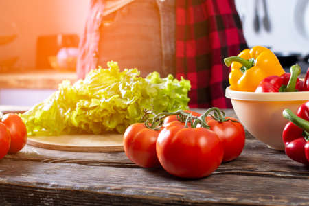 Tomatoes, bell peppers and greens, lie on a wooden table, ingredients for making salad, close-up of healthy food