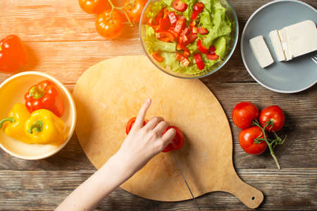 hands of a girl cut tomates on a wooden table, the process of making vegetarian salad, close-up cutting of vegetables and greens Stockfoto