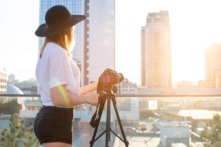 young girl photographer with a camera and a tripod on a background of the city, she photographs at sunset, a woman shoots a video Stok Fotoğraf