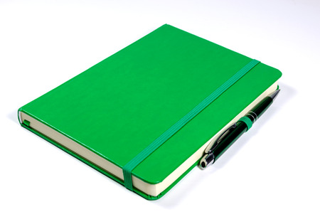 pad and pen: Green notebook and pen on white background