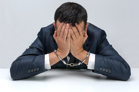 young  cuffs: White young businessman handcuffed. He is sitting at a table with face between his palms showing guilt and frustration